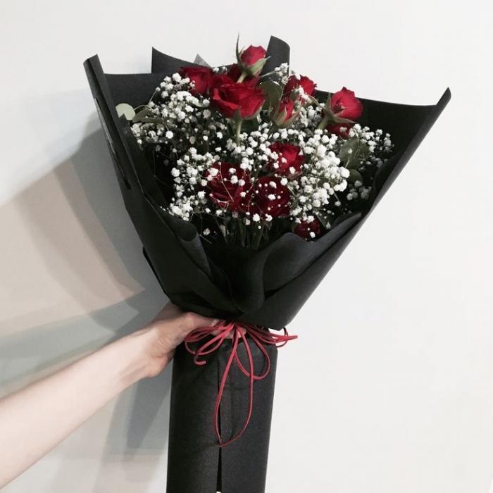 Букет из 7 красных роз в черном крафте