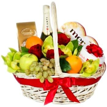 Корзина с фруктами, шампанским и цветами, украшенная красным бантом